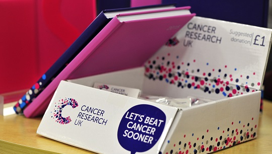 Cancer Research UK notesbooks and pin badges for sale in shop