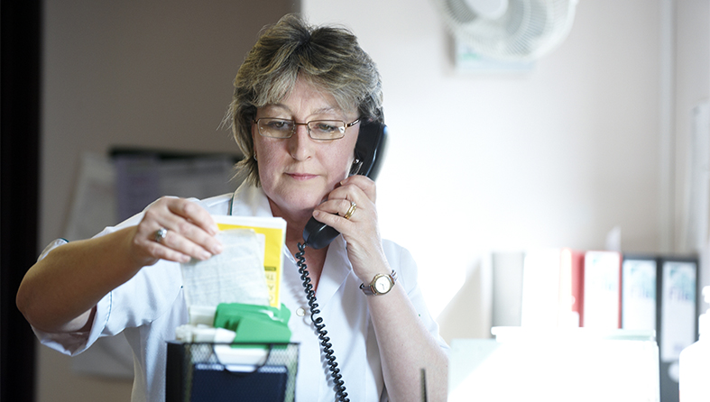 Nurse on the phone referring to patient notes