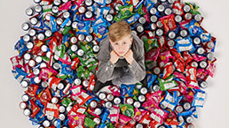 Boy sitting on fizzy drink cans and packets of junk food