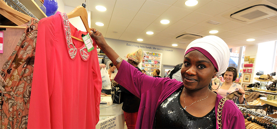 Photo of a shopper browsing at a Cancer Research UK shop. She is holding a pink top she has chosen from the rack.