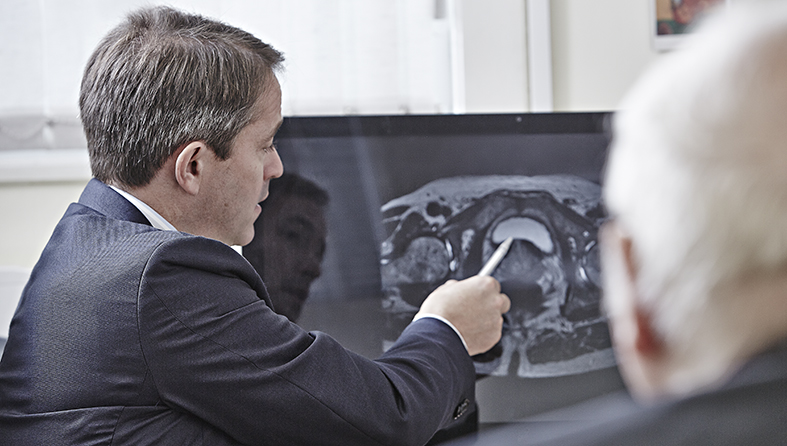Doctors look at a scan of a patient's abdomen
