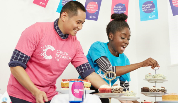 Two people setting up for a bake sale to fundraise for Cancer Research UK