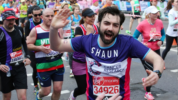 Cancer Research UK runner taking on London marathon with hand raised ready for a high five.