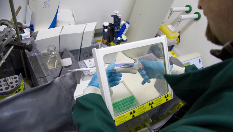 Researcher behind a screen working with radiation