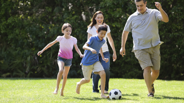 Happy family plays football in park