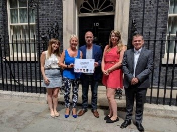 4 people standing outside No 10 Downing Street