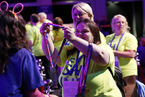 Shine Night Walk 2016 volunteer handing out medals at finish line