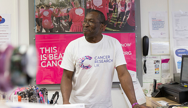 A shop volunteer smiles as he looks after the till in a Cancer Research UK shop