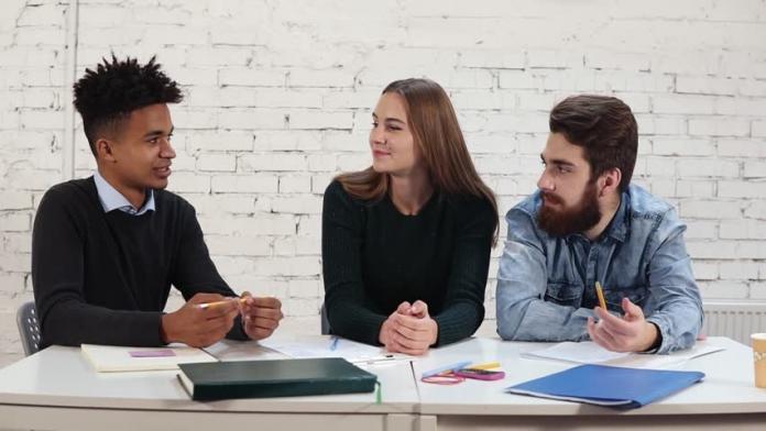 Three students sitting at a tablr