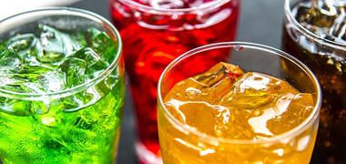 Different coloured fizzy drinks in glasses