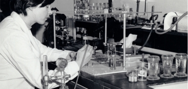 Black and white photograph of a scientist working in an old laboratory
