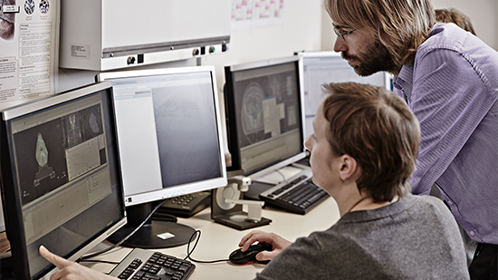 Image of two people at a computer