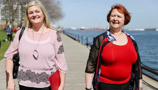 Two women walking along a river front in work clothing