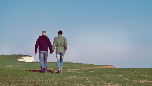 a couple walking along the top of a cliff