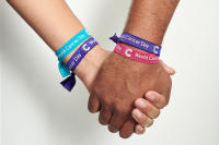 Friends holding hands wearing World Cancer Day unity bands
