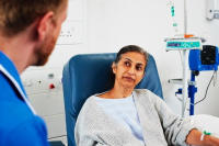 A woman sat in a hospital chair with a doctor