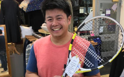 Alex Teow holding Rafael Nadal's tennis racket in the Wimbledon Cancer Research UK shop