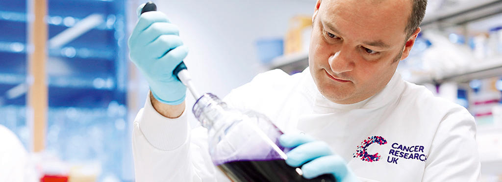 A Cancer Research scientist injects liquid into a flask