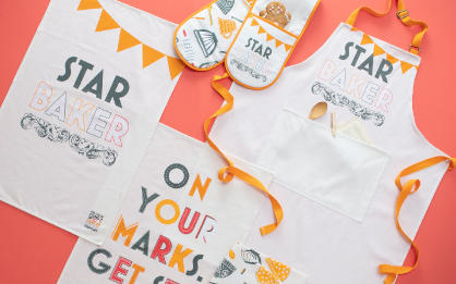 The Great Stand Up To Cancer Bake Off 2020 merchandise, including tea towels, oven gloves, and Star Baker apron
