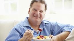 Overweight man eats a fruit salad