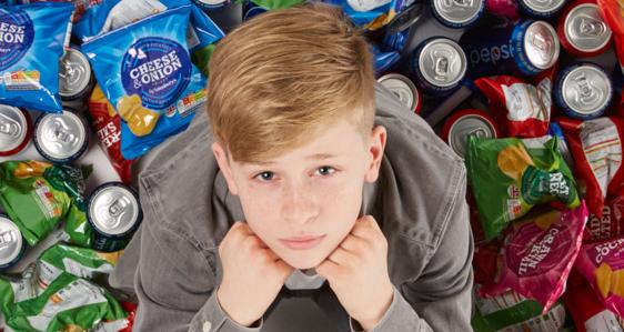 Boy in school uniform surrounded by junk food