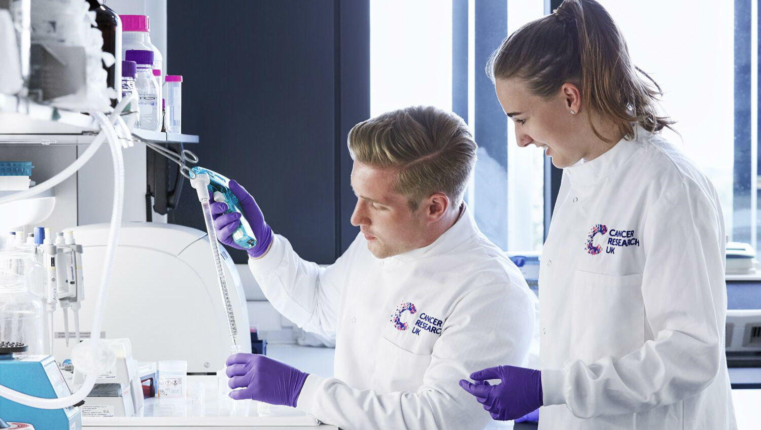 Scientist in lab with PhD student looking over shoulder