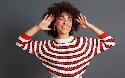 A smiling model wearing a red and white striped jumper.