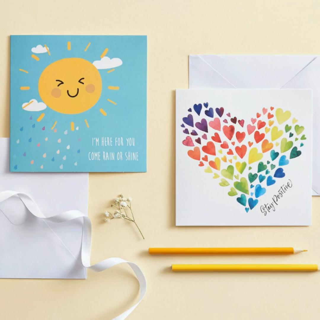 Two greetings cards. One shows a smiling sun and text 'I'm here for you come rain or shine', the other a heart shape with caption 'Stay positive'.