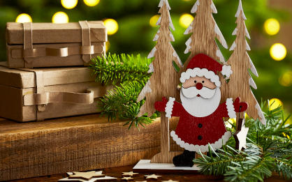 A wooden Father Christmas and snowy tree decoration