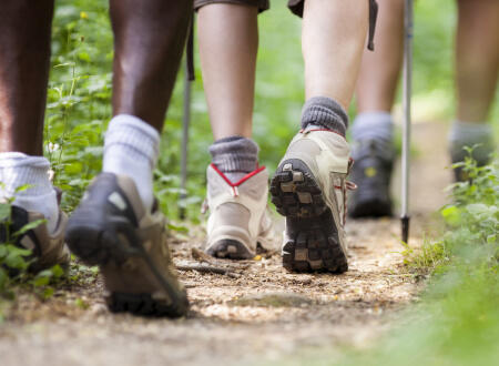 A close up of three people's walking boots in the countryside