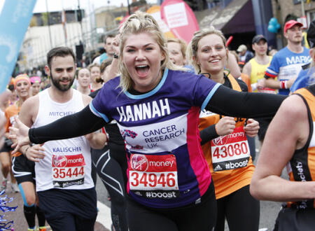 A young woman smiling while running a marathon surrounded by other runners