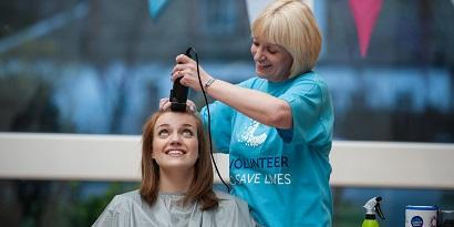A girl getting her head shaved by a woman in a blue cruk tshirt