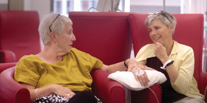 A cancer patient receiving a treatment while her friend sits next to her and holds her hand