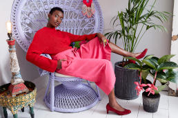 A model, wearing a red top, pink skirt and red shoes, reclining in a large wicker chair
