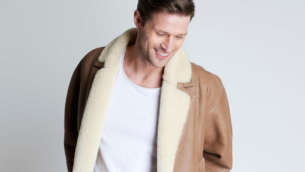 A male wearing a wool-lined brown sheepskin aviator jacket and white t-shirt.