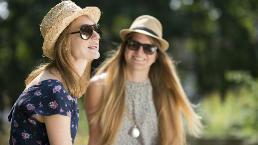 Girls wear straw hats in the sun