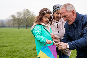 Photo of family playing with a kite