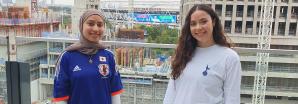 Two girls smiling wearing football shirts