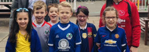 A group of smiling children wearing football shirts at school