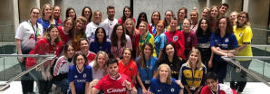 A big group of people smiling wearing football shirts at work