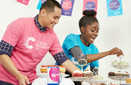 two people fundraising for world cancer day 2020 by setting up a bake sale