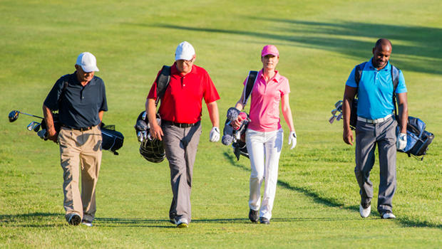4 people walking along golf course.