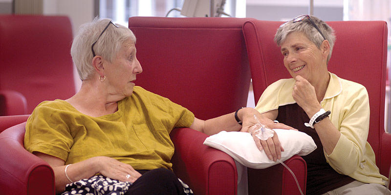 Two women talk and laugh while one receives cancer treatment