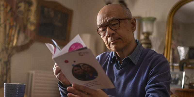 Photo of a man reading a Cancer Research UK pamphlet
