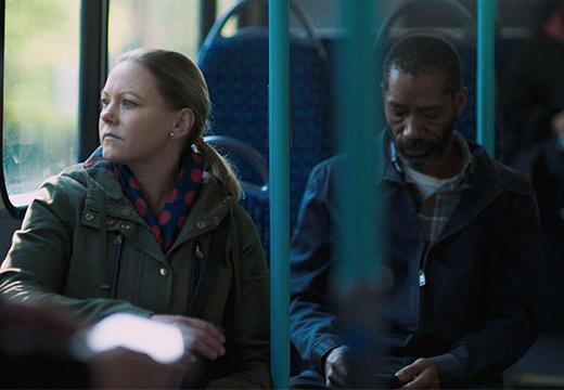 Two people sit on a bus as one looks out the window