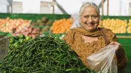 Older woman shops for vegetables at the green grocer