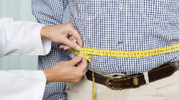 Overweight man's waist is measured by doctor