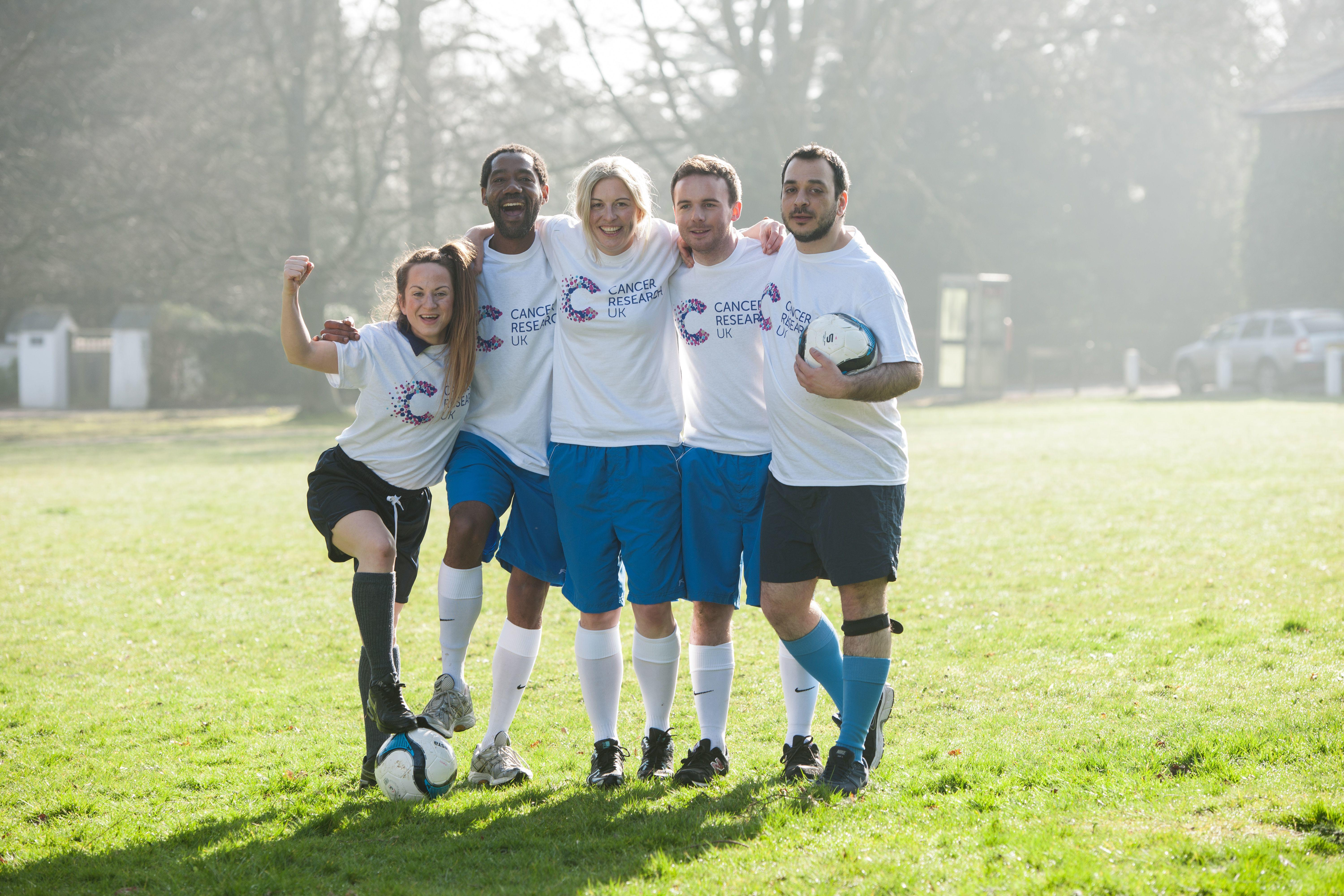 Five people with their arms around each other wearing football kit and holding a football