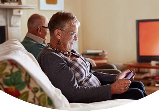 Person seated comfortably looking at tablet