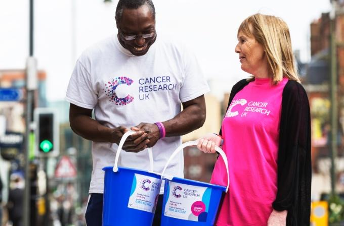 Two volunteers with donation buckets out on the streets collecting money for Cancer Research UK